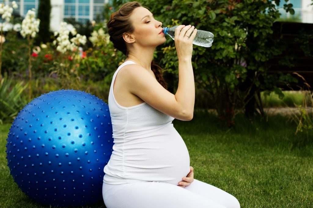 Pregnant lady drinking water from a plastic bottle