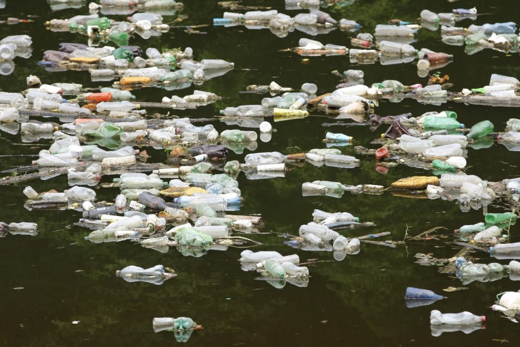 water surface pollution on a river - many floating plastic bottles