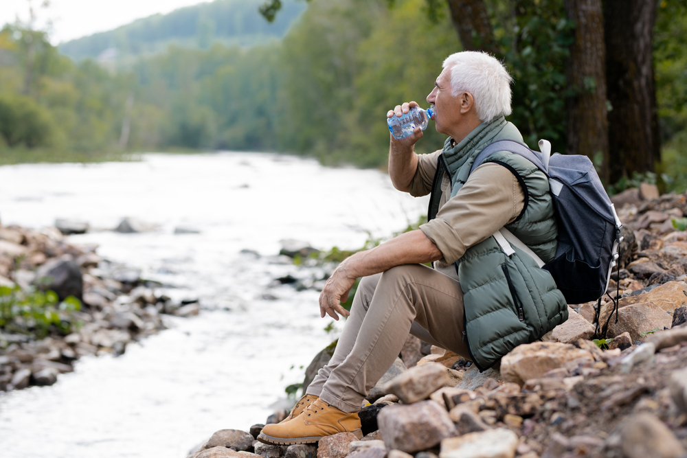 Stay Hydrated while travelling with a ZeroWater portable filtration solution this summer - a tired mature backpacker drinking water from plastic bottle while sitting on river bank in natural environment