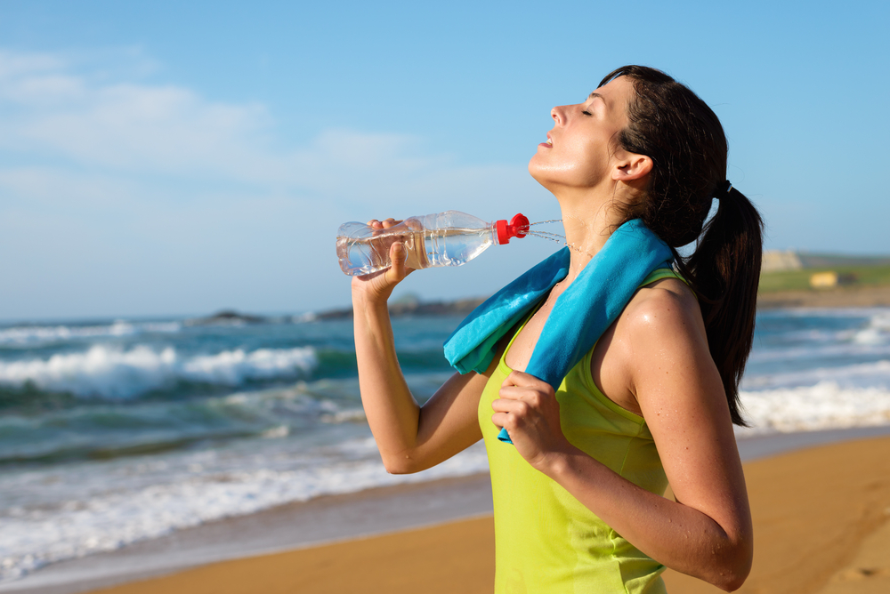 Stay Well-Hydarated at all times when travelling this summer. - Fitness woman spraying water in her body and drinking after running in beach. Female athlete sweating and exhausted after working out.