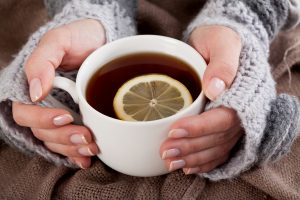 The Health Benefits of Tea, a news article byZeroWater Uk - Woman's hand holding cup of tea with lemon on a cold day
