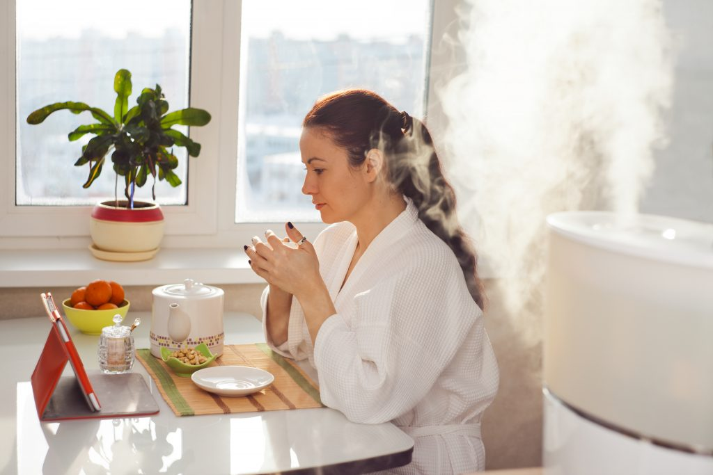 No more humidifier fever with filtered water! - Woman drinking tea and reading her tablet near humidifier.